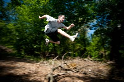runner jumping over log