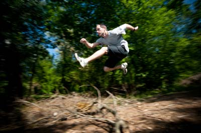 runner jumping over log